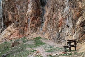 Lavička pod skalnou stenou a visiace lano, ktoré vás môže pomýliť